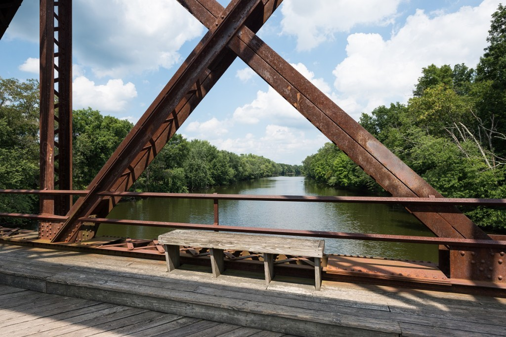 Bench on the Wallkill River Rail Trail Bridge in Upstate New York with a view of the river through the bridge structure.